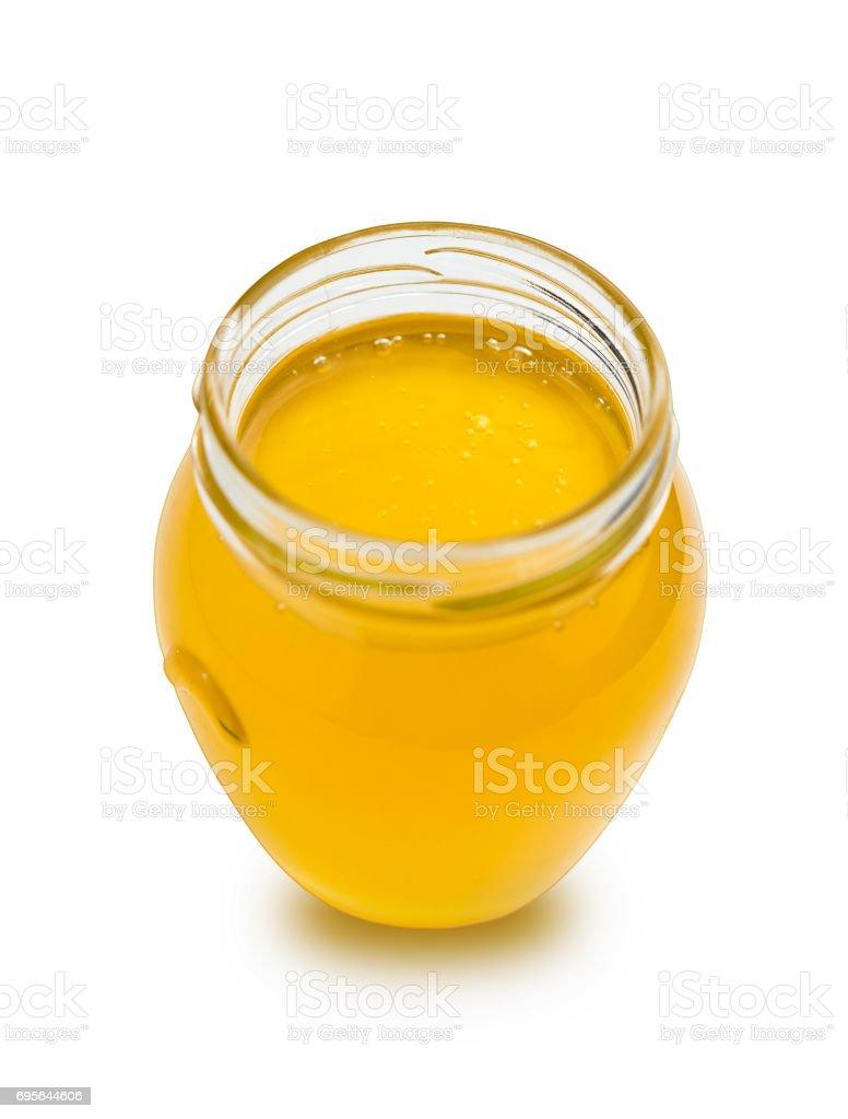 Sweet honey in glass jar on white background. stock photo