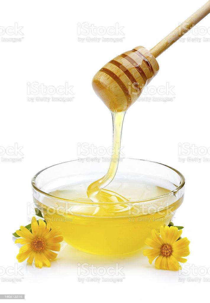 Sweet honey pouring from wooden dipper in glass bowl isolated royalty-free stock photo