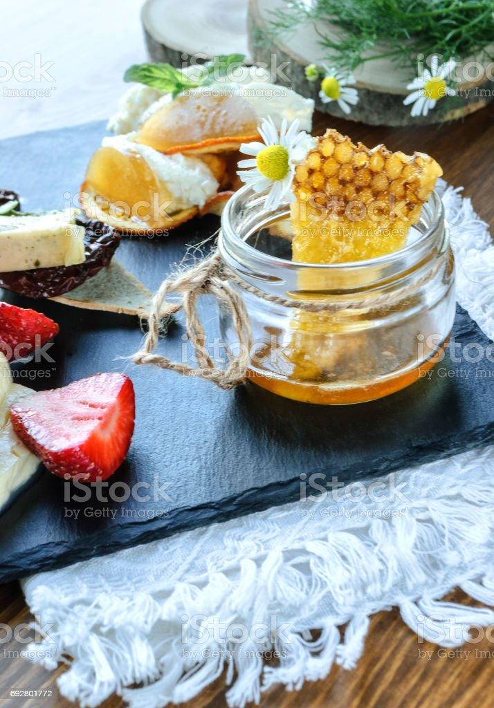 Sweet honeycombs and bank with honey on wooden table on natural background stock photo