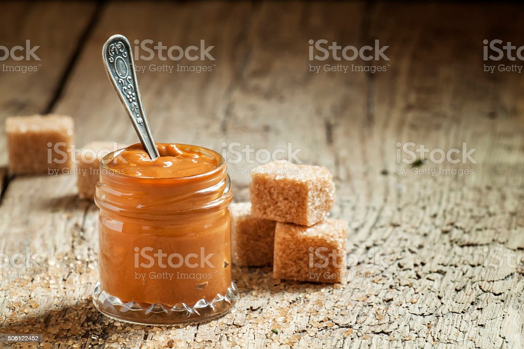 Sweet liquid caramel in a small jar stock photo