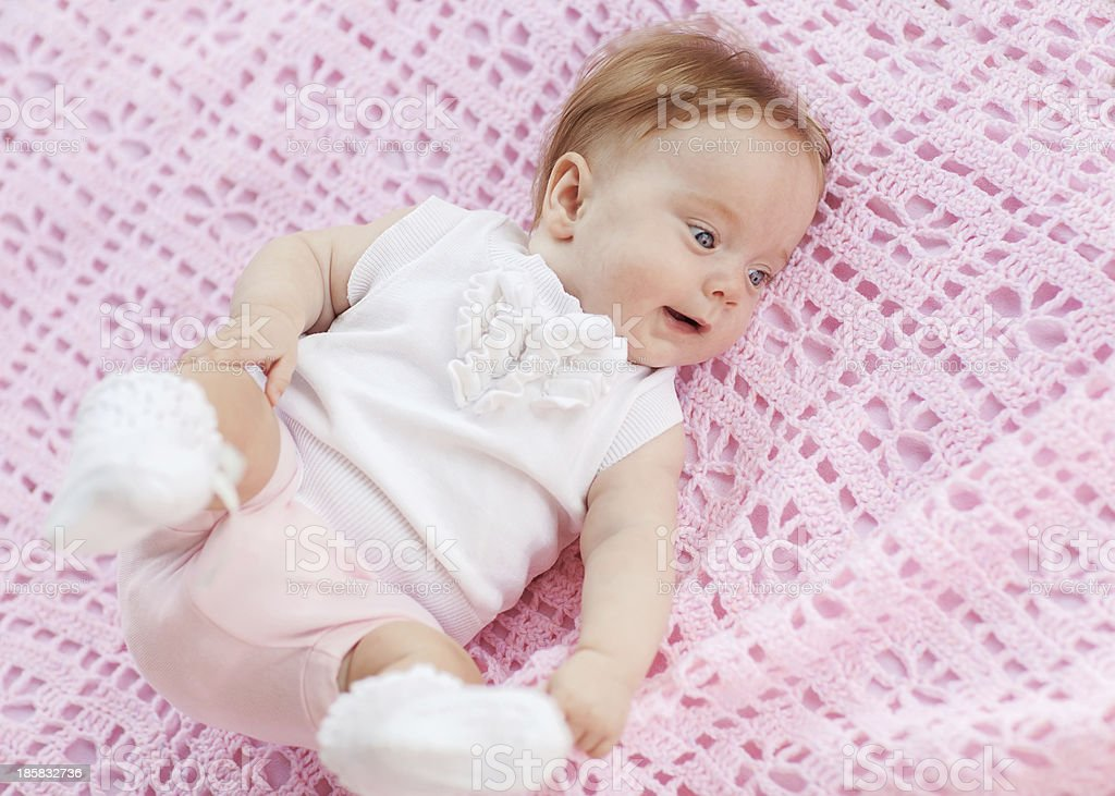 Sweet little baby girl lying on her back. royalty-free stock photo