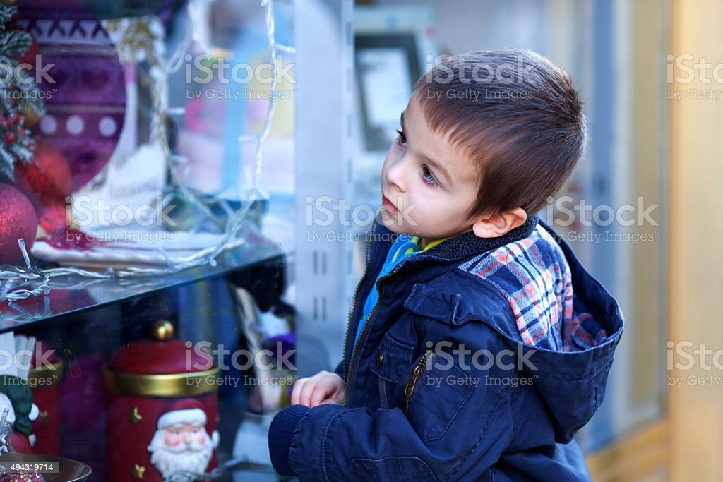 Sweet little boy, looking through a window in shop stock photo