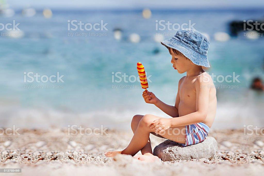 Sweet little child, boy, eating ice cream on the beach stock photo
