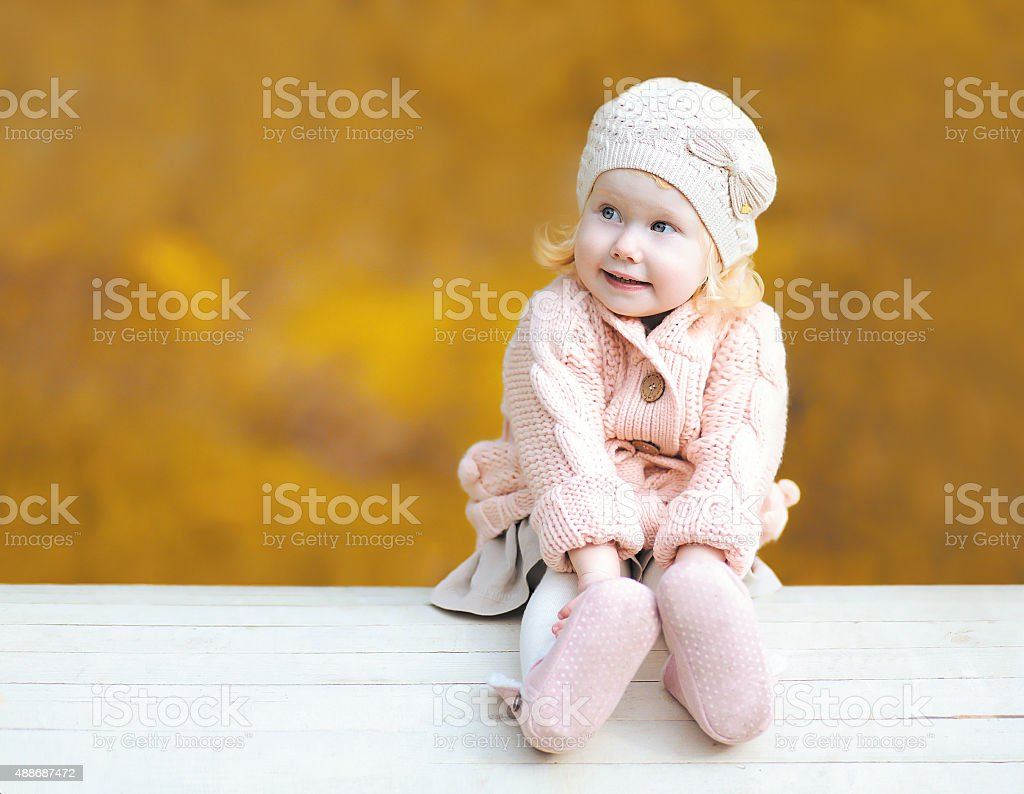 Sweet little child wearing a knitted clothes in autumn day stock photo