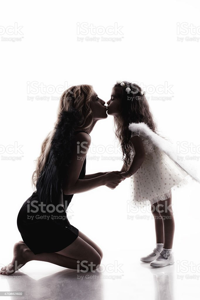 sweet little girl and mother with angel wings posing stock photo