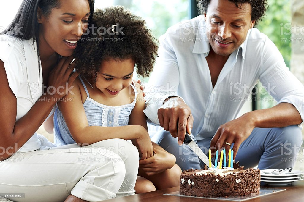 Sweet little girl celebrating birthday with her family royalty-free stock photo