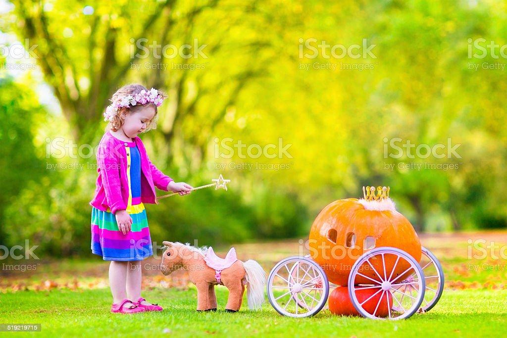 Sweet little girl playing Cinderella in autumn garden stock photo