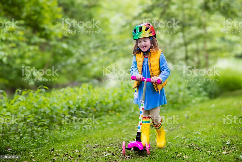 Sweet little girl riding a colorful scooter stock photo