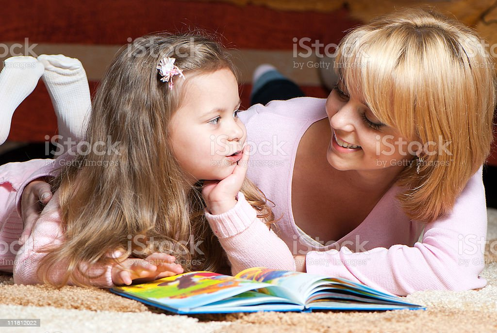 sweet  little girl with mother reading book stock photo