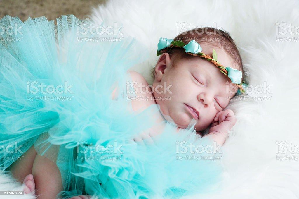Sweet little newborn girl in teal tutu sleeping. stock photo