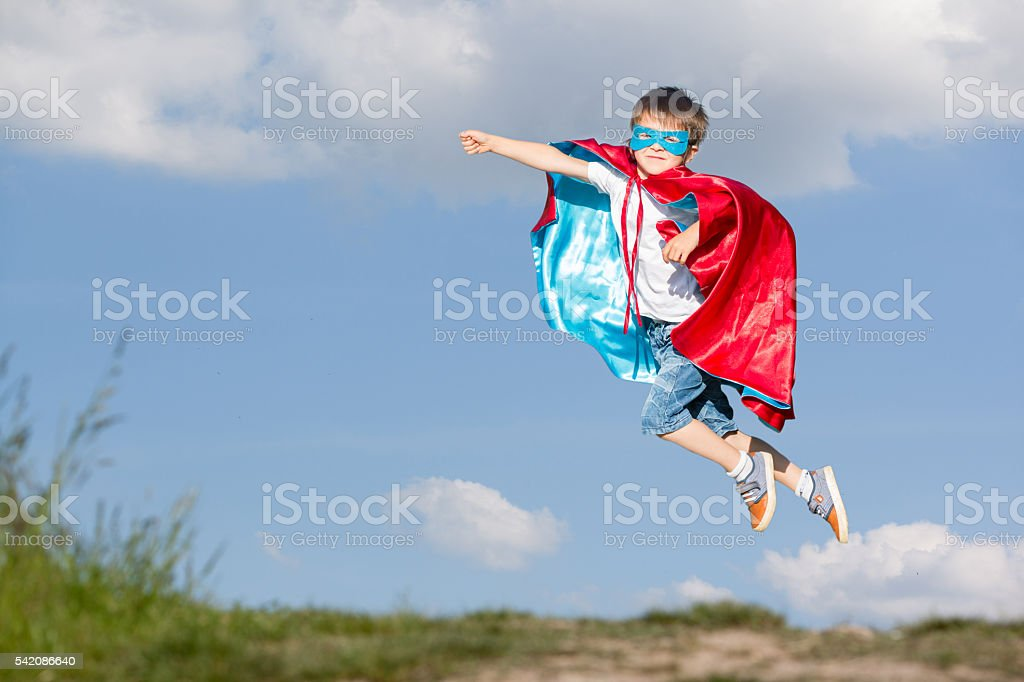 Sweet little preschool boy, playing superhero in the park stock photo
