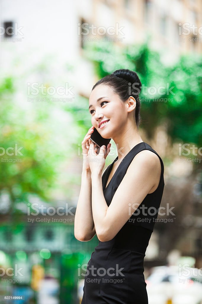 Sweet Looking Asian Girl On The Phone In The Street stock photo