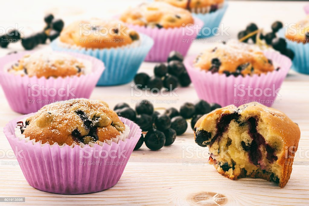 Sweet muffins with chokeberries (aronia) on white wooden table. stock photo
