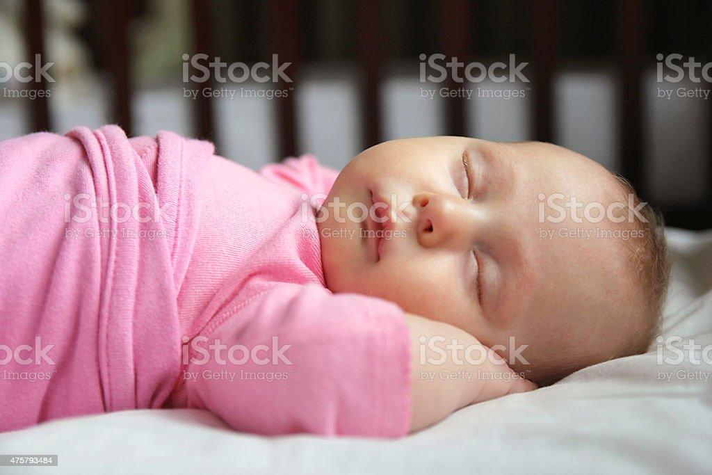 Sweet Newborn Baby Girl Asleep in Crib stock photo