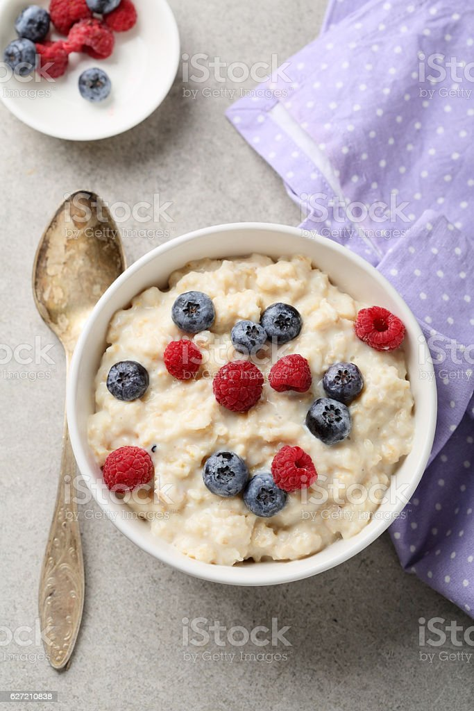 Sweet oat flakes with milk and berry stock photo