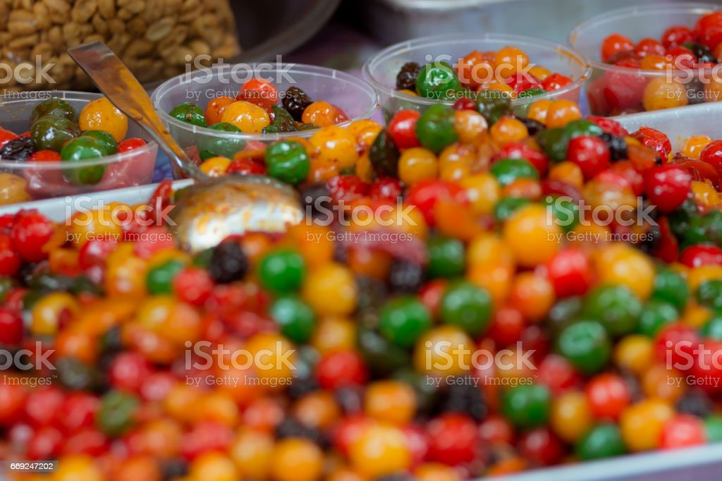 Sweet pickled colorful fruits for sale on a street food stall. stock photo