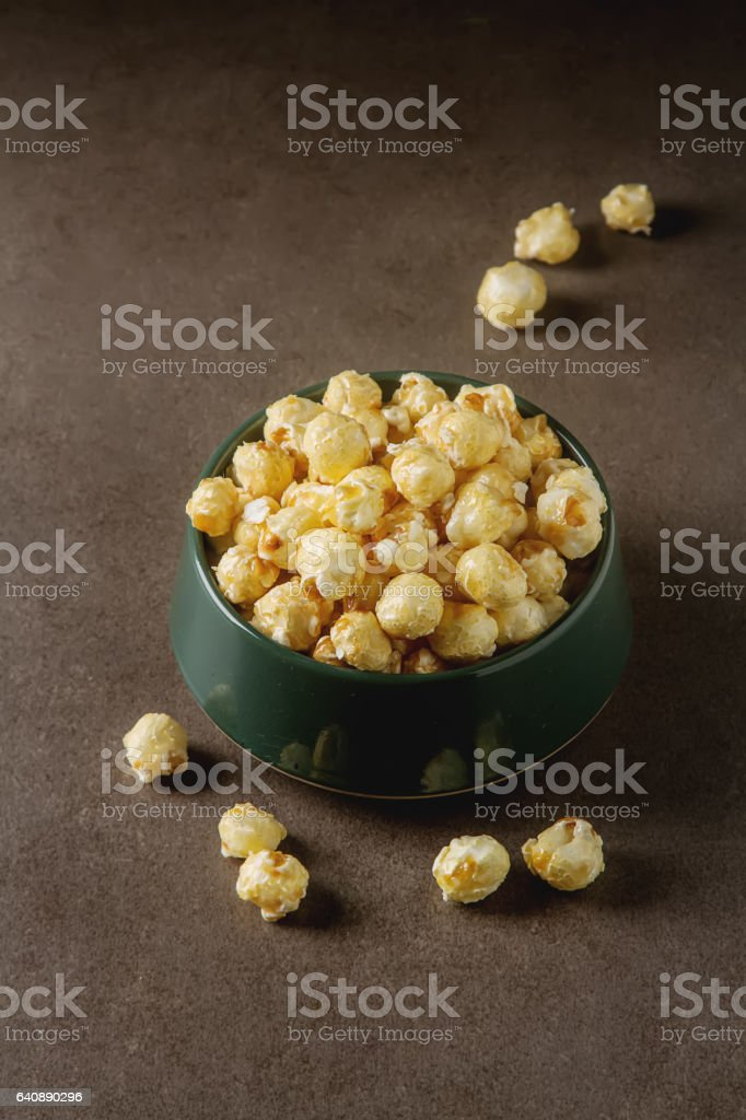 Sweet popcorn in a bowl. Gray background. Watch a movie. stock photo