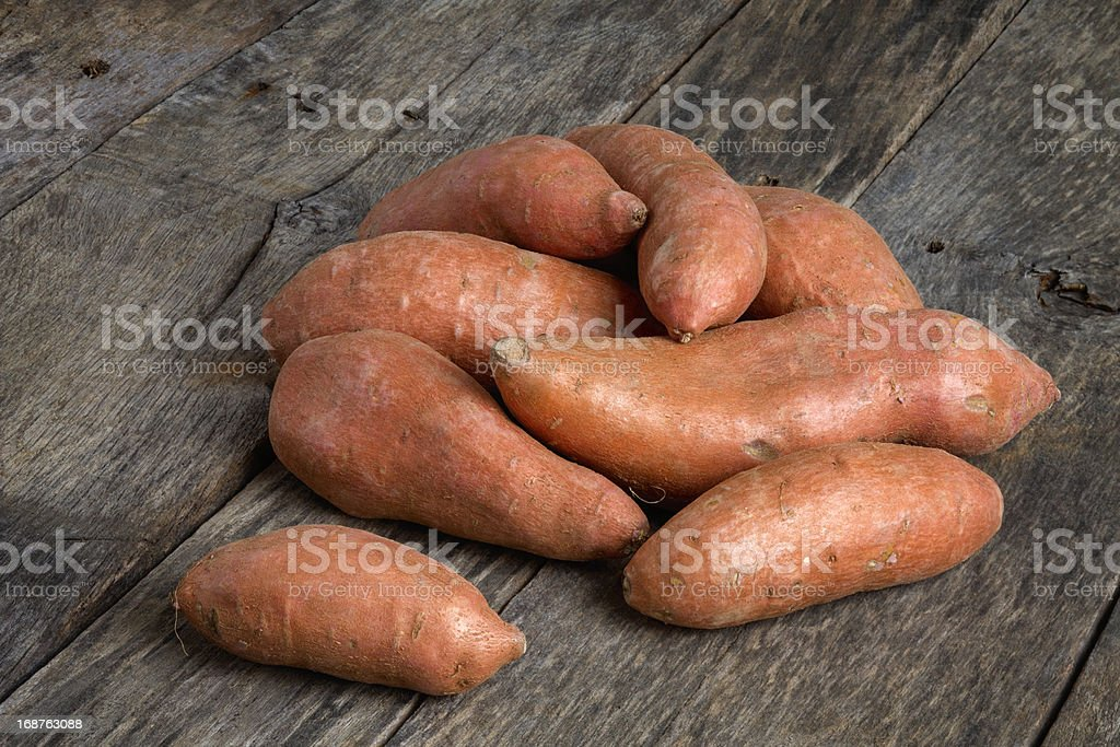 Sweet Potatoes On Rough Weathered Wood Table royalty-free stock photo