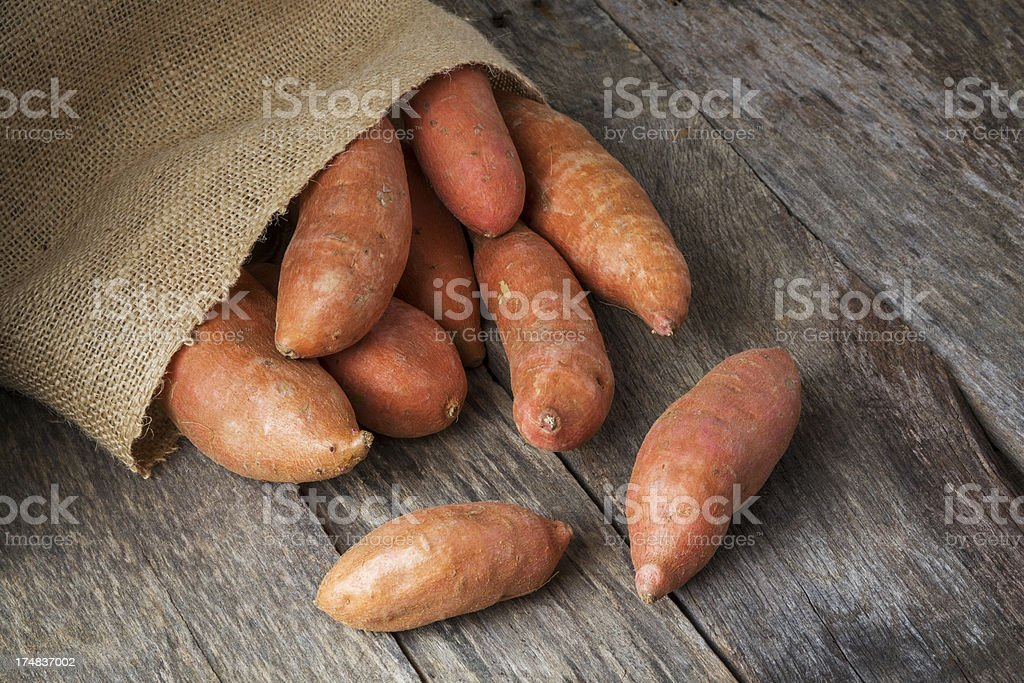 Sweet Potatoes Spilling From Burlap Bag stock photo