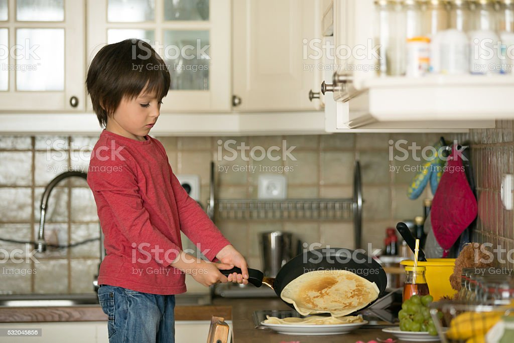 Sweet preschool child, helping his mom in the kitchen stock photo