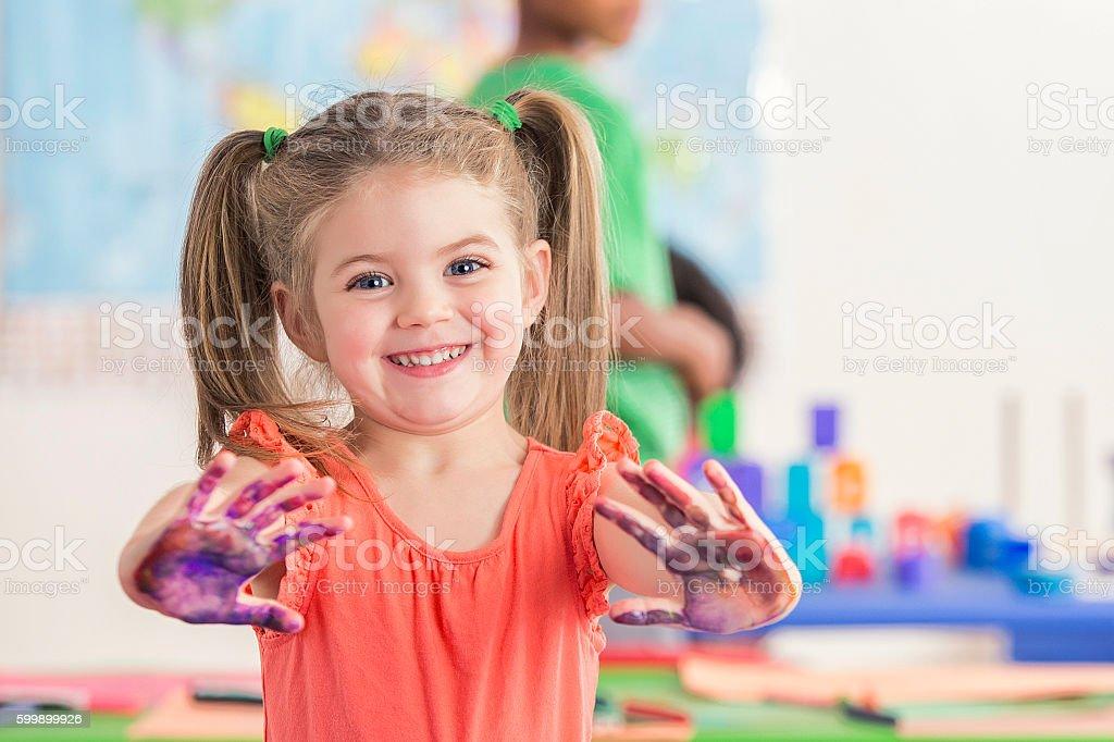Sweet preschooler has fun with finger paints stock photo