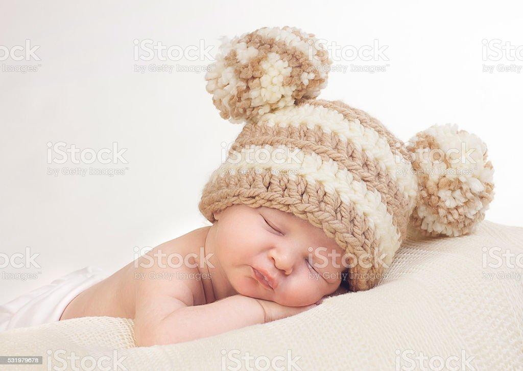 Sweet sleeping newborn with knitted pom pom hat stock photo