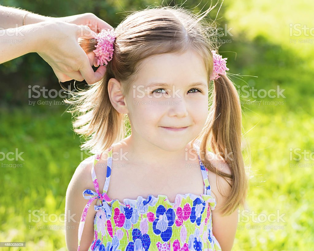 Sweet smiling little girl with her mom's hands making hairstyle stock photo