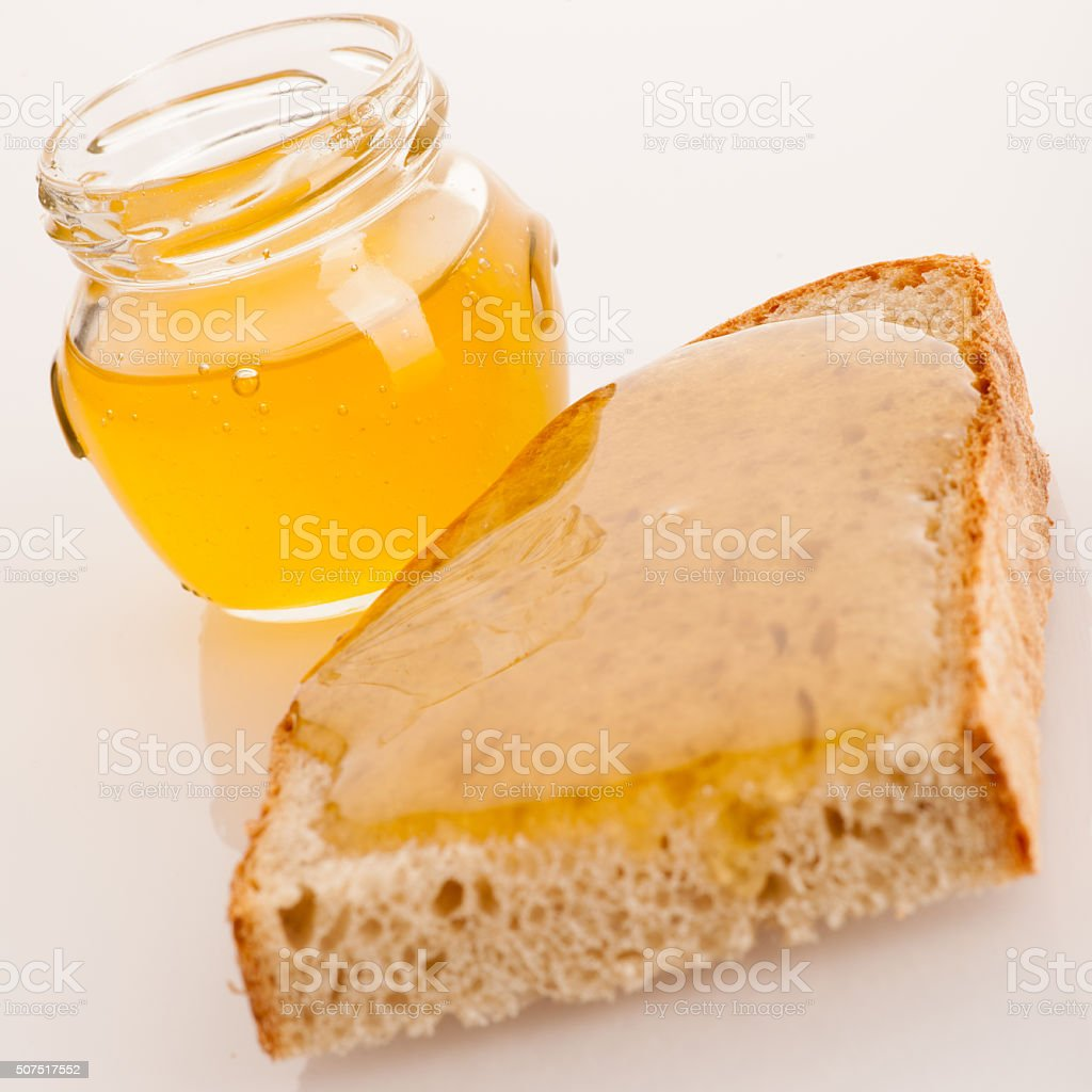 Sweet sticky golden honey on a slice of fresh bread stock photo