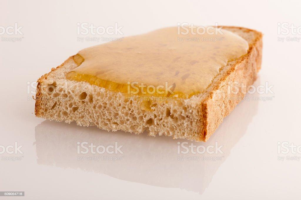 Sweet sticky golden honey on a slice of fresh bread. stock photo