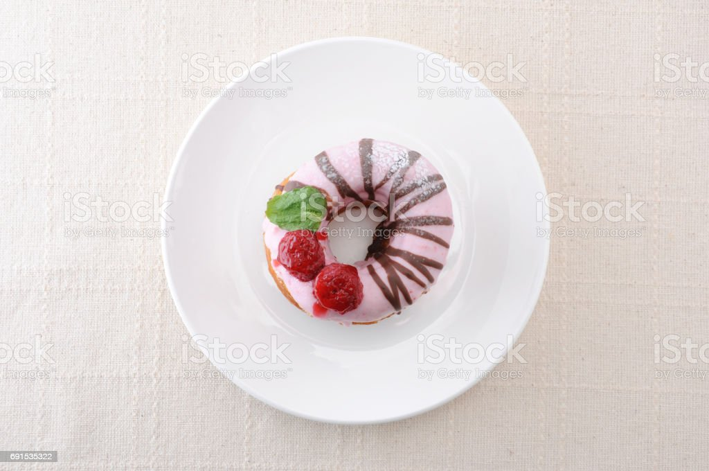 sweet strawberry cake doughnut on a plate on table stock photo