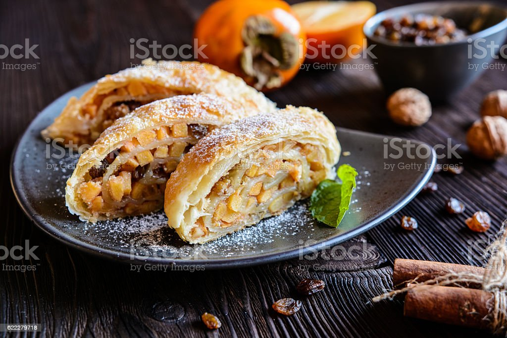Sweet strudel with persimmons, raisins and walnuts stock photo