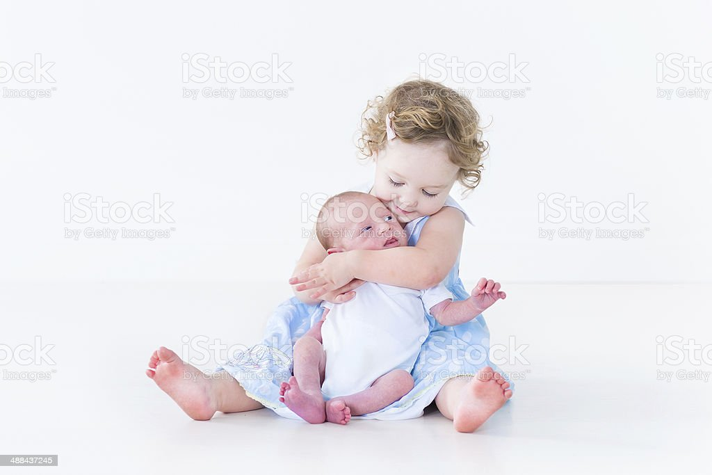 Sweet toddler girl in blue dress kissing her newborn brother stock photo