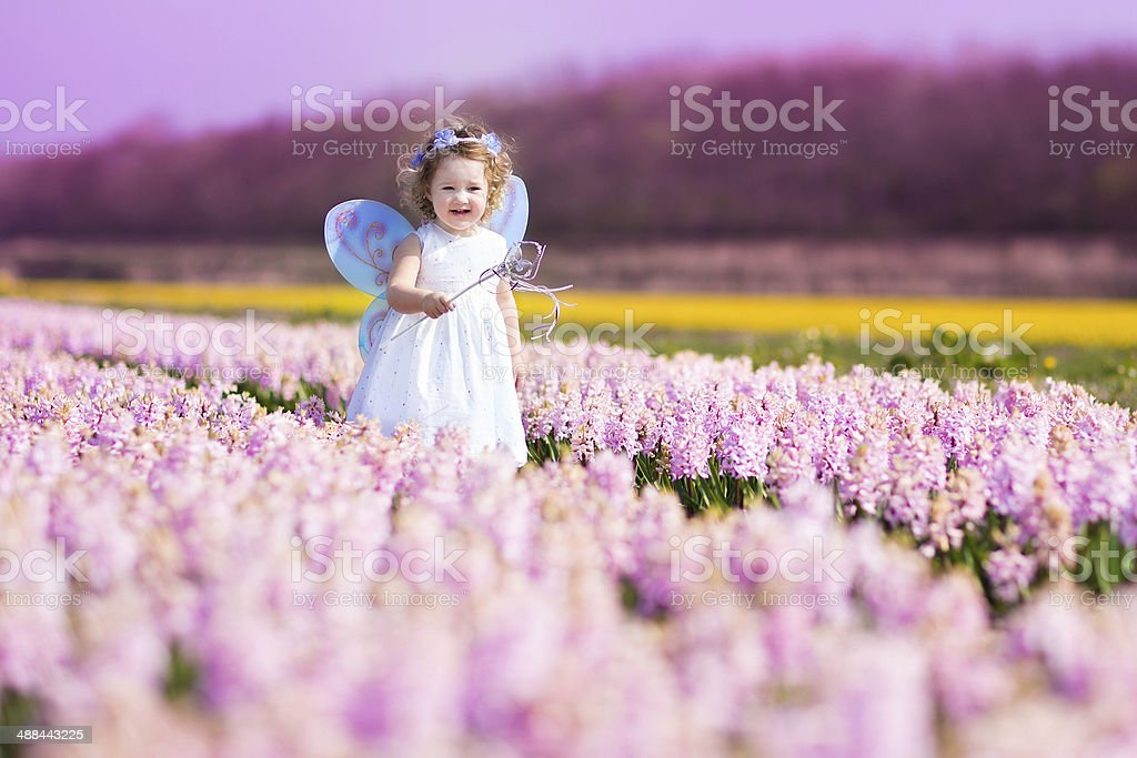 Sweet toddler girl in fairy costume on a flower field stock photo