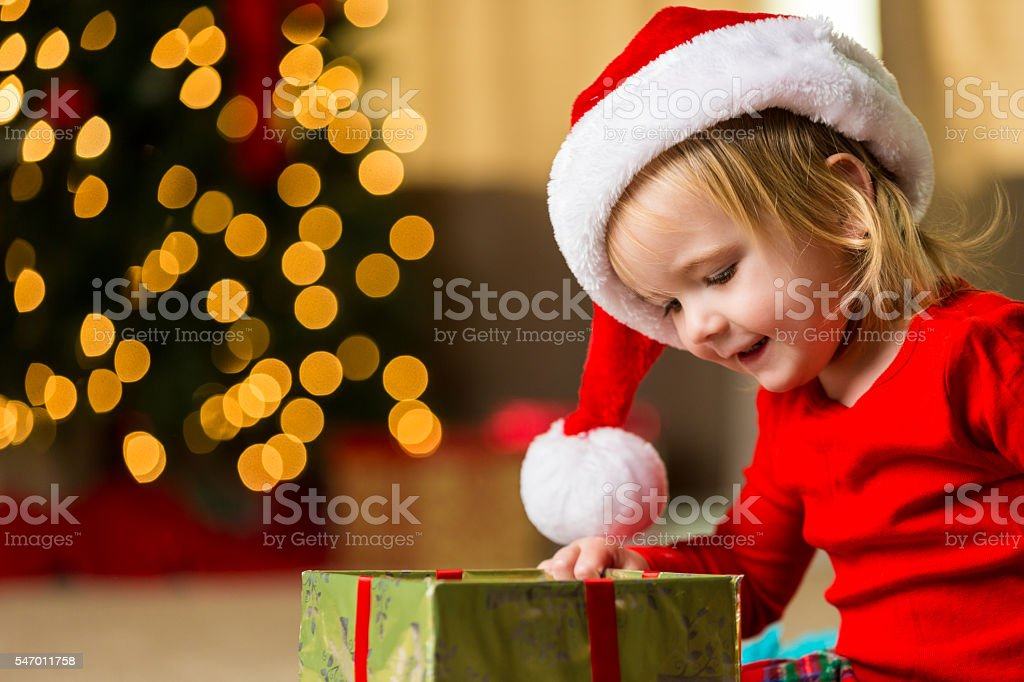 Sweet toddler girl looking into christmas box stock photo
