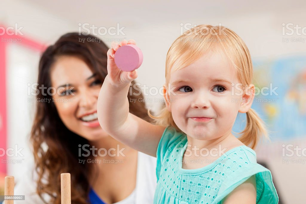 Sweet toddler girl plays with blocks in daycare classroom stock photo