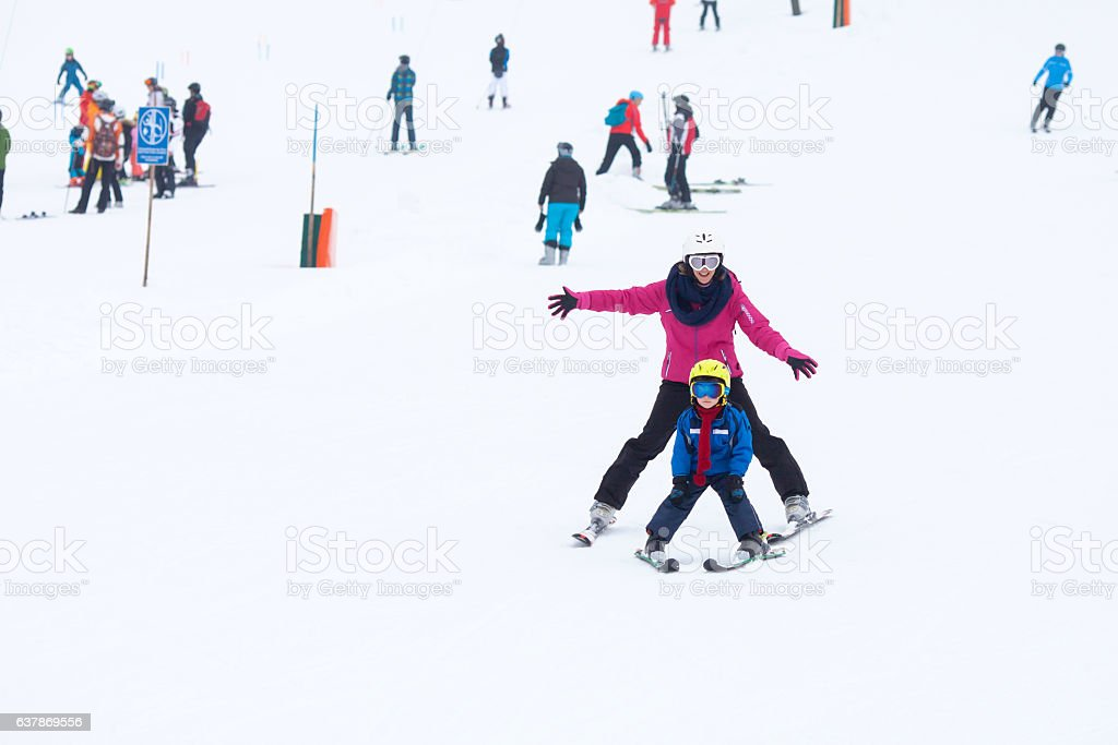 Sweet young boy and his mother, learning to ski stock photo