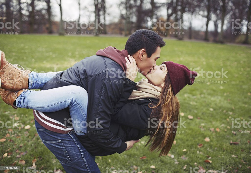 Sweet young couple sharing a kiss while on date stock photo