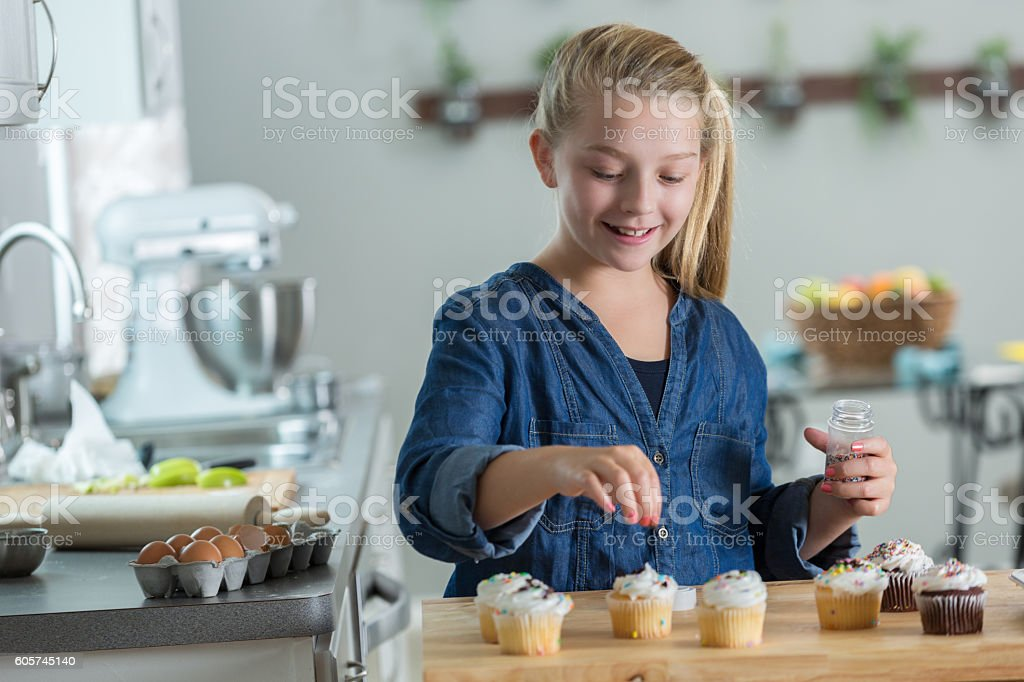Sweet young girl uses sprinkles to decorate cupcakes stock photo
