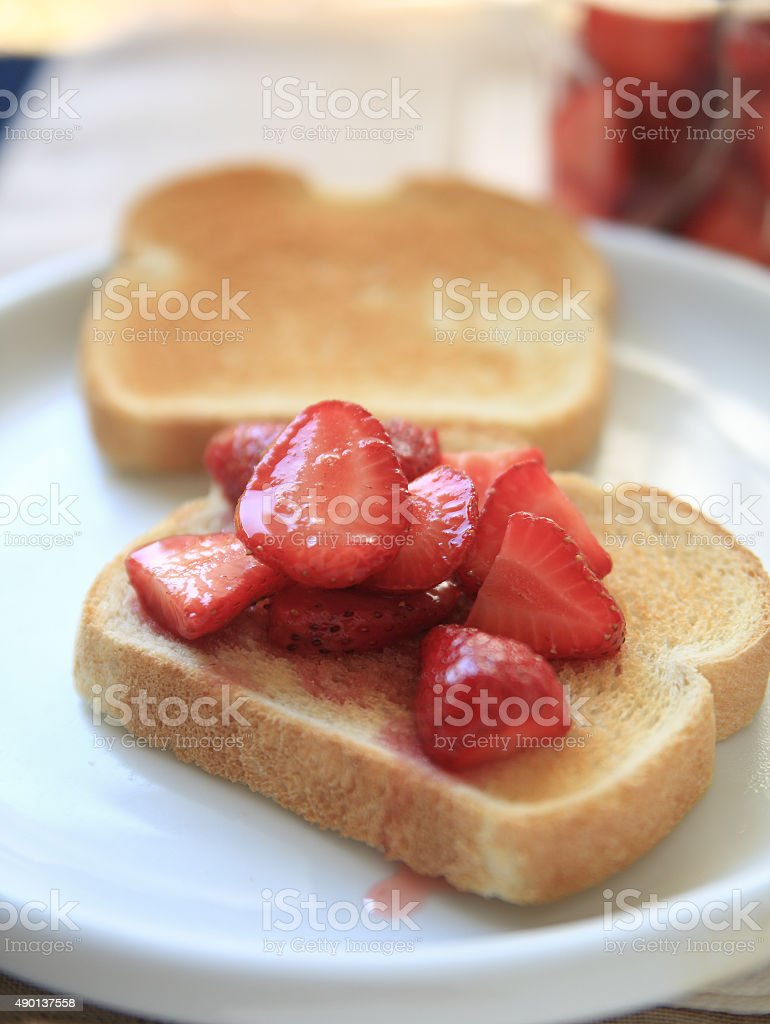 Sweetened strawberries on toast stock photo