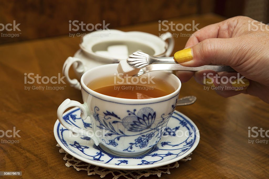 Sweetening tea sugar cube stock photo