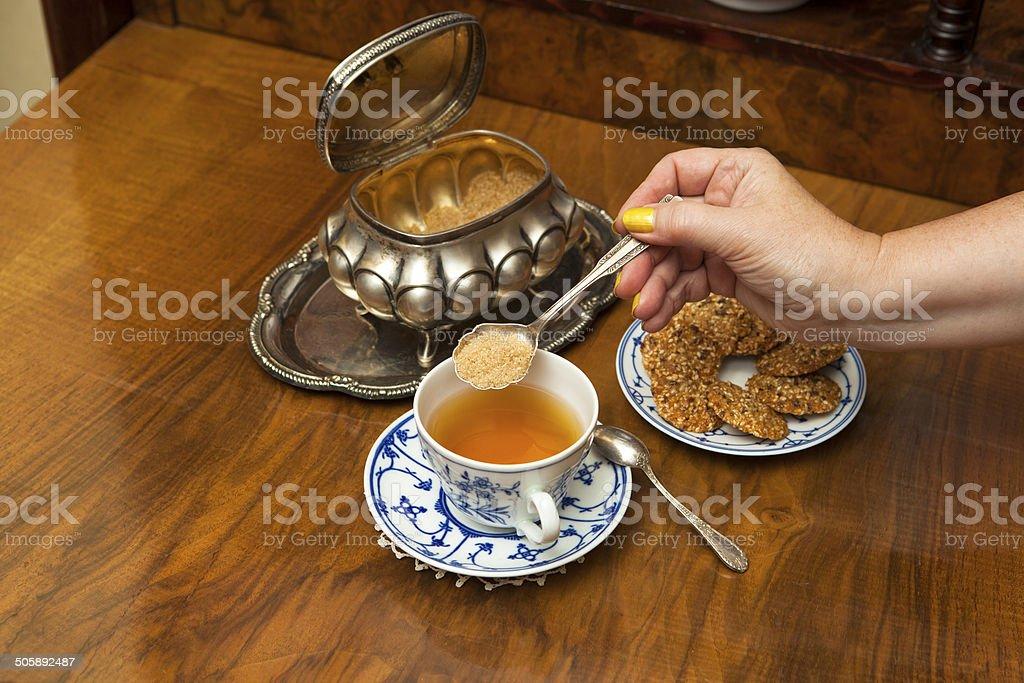 Sweetening tea with brown sugar royalty-free stock photo