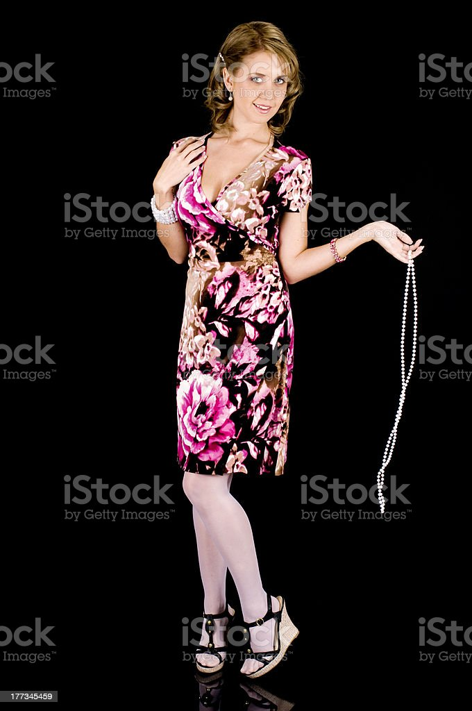 Sweet-Faced Model in Colorful Spring Outfit Removing her Pearl Necklace. royalty-free stock photo