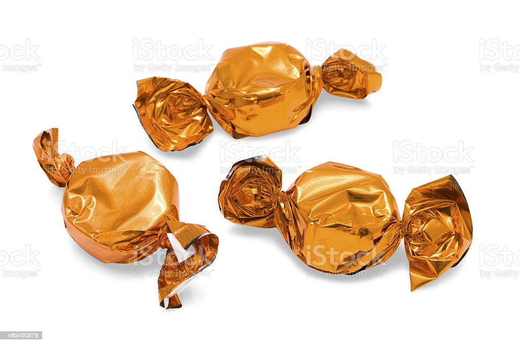 Sweets in orange foil wrappers on isolated a white background stock photo