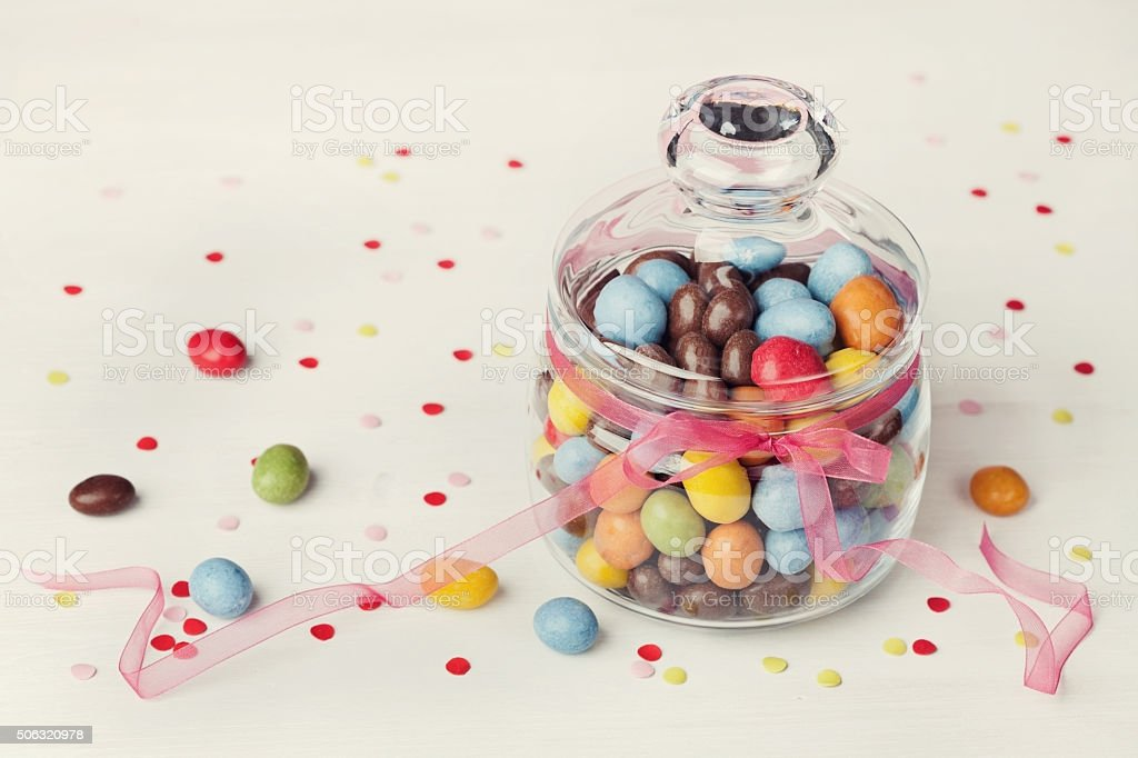 Sweets or candy in jar with confetti, holiday concept stock photo
