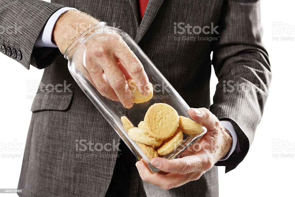 Sweet-toothed businessman with hand in the cookie jar, literally stock photo