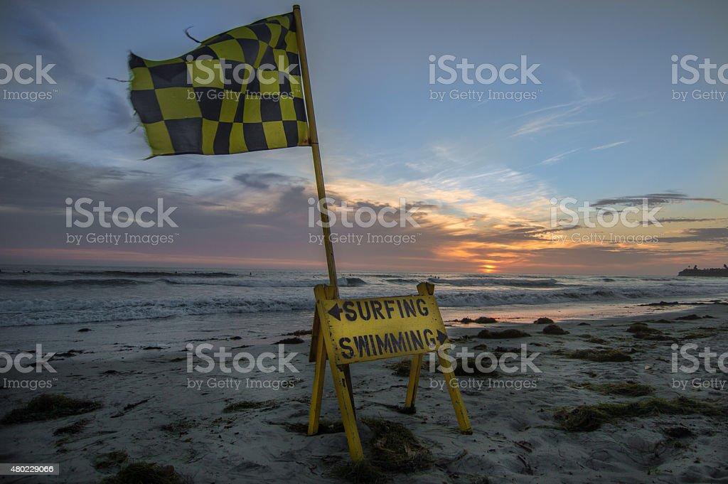 swim area flag at sunset stock photo