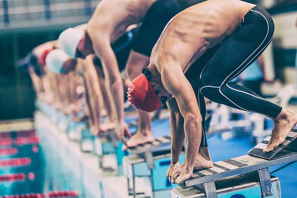 swimmer crouching on starting block ready to jump stock photo