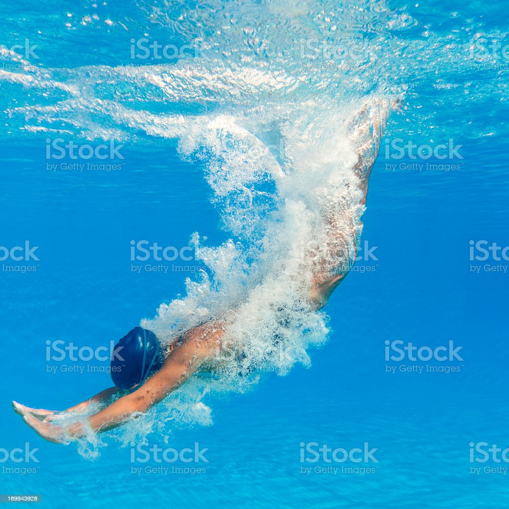 Swimmer diving into a clear blue pool stock photo