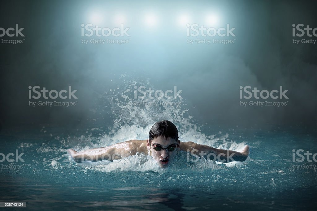 Swimmer in waterpool. Butterfly style of swimming stock photo
