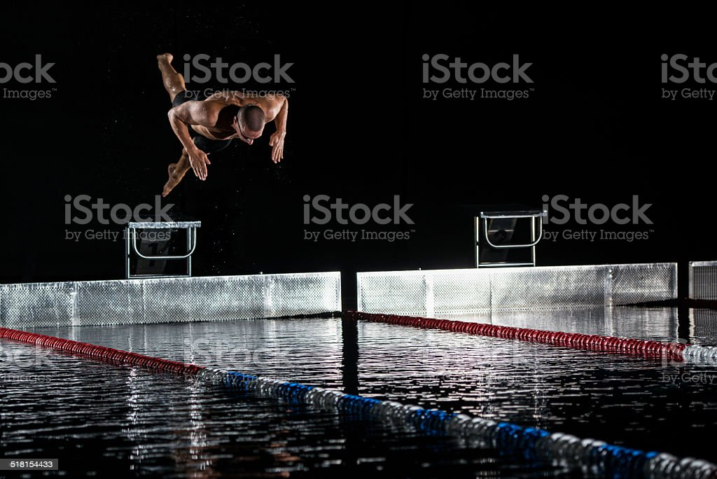 Swimmer Jumping Off The Starting Block stock photo
